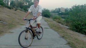 Glimlachende personenvervoerfiets, stadspark dichtbij rivier, luchtschot stock videobeelden