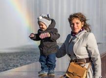 Glimlachende peuter met zijn moeder die zich dichtbij regenboog bevinden Royalty-vrije Stock Fotografie