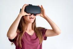 Glimlachende positieve vrouw die de virtuele hoofdtelefoon van werkelijkheidsbeschermende brillen dragen, vr doos Verbinding, tec stock afbeeldingen