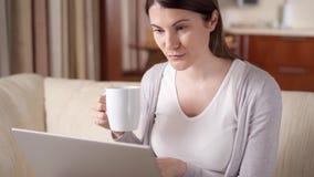 Glimlachende professionele vrouw die aan laptop computer werken die thuis koffie drinken Huis-bureau concept stock video
