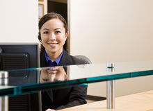 Glimlachende receptionnist met telefoonoortelefoon Stock Afbeelding