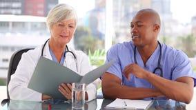 Glimlachende rijpe arts die documenten tonen aan een verpleegster stock video