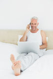 Glimlachende rijpe mens die cellphone en laptop in bed met behulp van Royalty-vrije Stock Fotografie