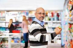 Glimlachende rijpe mens die in de supermarkt winkelt Stock Afbeelding