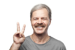 Glimlachende rijpe mens die die overwinningsteken tonen op wit wordt geïsoleerd Stock Foto