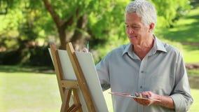 Glimlachende rijpe mens die op een canvas trekken stock videobeelden
