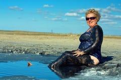 Glimlachende rijpe mollige vrouw die modderbehandeling neemt Royalty-vrije Stock Afbeeldingen