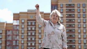 Glimlachende rijpe oude vrouw die hand omhoog met sleutels opheffen stock video