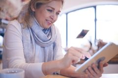 Glimlachende rijpe vrouw die aan tablet in koffie werkt Stock Afbeeldingen