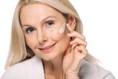 glimlachende rijpe vrouw die kosmetische room toepassen royalty-vrije stock afbeelding