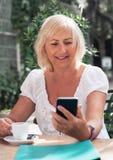 Glimlachende rijpe vrouw die op smartphone en het drinken koffie i spreken royalty-vrije stock foto