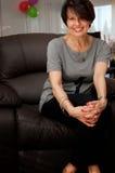 Glimlachende rijpe vrouw op leunstoel Stock Fotografie