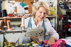 Glimlachende rijpe vrouwenkleermaker die naaimachine met behulp van Royalty-vrije Stock Afbeeldingen