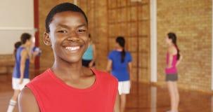 Glimlachende schooljongen die een basketbal houden terwijl team het spelen op achtergrond stock video
