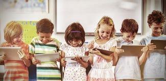Glimlachende schoolkinderen die digitale tabletten gebruiken stock fotografie