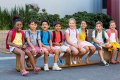 Glimlachende schoolkinderen op zetel stock foto