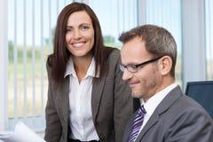 Glimlachende secretaresse met haar werkgever stock foto's