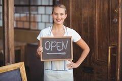 Glimlachende serveerster die bord met open teken tonen stock afbeeldingen