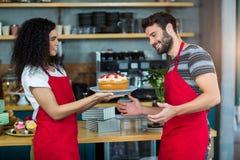 Glimlachende serveerster die een plaat van cake geven aan kelner Stock Afbeelding
