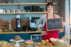 Glimlachende serveerster die lei met open teken tonen Stock Afbeeldingen