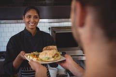 Glimlachende serveerster die plaat met voedsel geven aan medewerker Stock Afbeeldingen