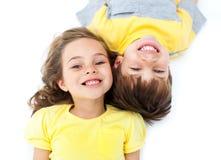 Glimlachende siblings die op de vloer liggen Stock Afbeelding