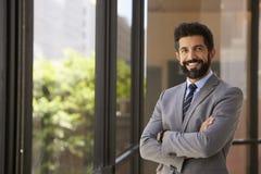 Glimlachende Spaanse die zakenman met wapens, aan camera worden gekruist stock fotografie