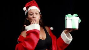 Glimlachende spiervrouw met gift het stellen in santauitrusting stock video