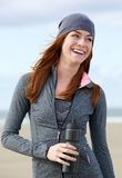 Glimlachende sportieve vrouw die zich in openlucht met waterfles bevinden Royalty-vrije Stock Fotografie