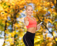 Glimlachende sportieve vrouw met smartphone Royalty-vrije Stock Foto's