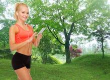 Glimlachende sportieve vrouw met smartphone en oortelefoons Royalty-vrije Stock Foto's