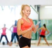 Glimlachende sportieve vrouw met smartphone en oortelefoons Royalty-vrije Stock Foto