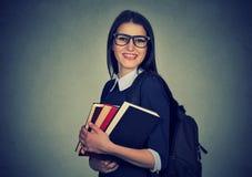 Glimlachende student die een rugzak en het houden van stapel boeken dragen Stock Fotografie