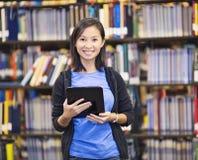 Glimlachende student die een tabletcomputer met behulp van Stock Foto's