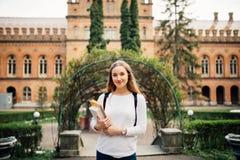Glimlachende studente openlucht met zak en notitieboekje dichtbij Universiteit stock afbeeldingen