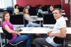 Glimlachende studenten in computerklasse Stock Afbeeldingen