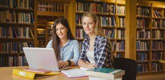 Glimlachende studenten die laptop met behulp van stock foto