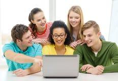Glimlachende studenten die laptop op school bekijken Stock Foto's