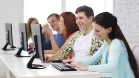 Glimlachende studenten die met computers op school werken stock videobeelden