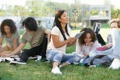 Glimlachende studenten die in openlucht bestuderen Opzij het kijken royalty-vrije stock foto's