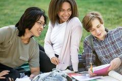 Glimlachende studenten die in openlucht bestuderen Opzij het kijken stock foto