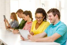 Glimlachende studenten die tabletpc bekijken op school stock afbeelding