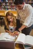 Glimlachende studenten die terwijl het zitten bij lijst samenwerken Stock Foto