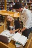 Glimlachende studenten die terwijl het zitten bij lijst samenwerken Stock Foto's