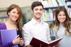 Glimlachende studenten in een bibliotheek Royalty-vrije Stock Fotografie
