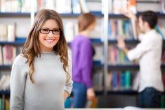 Glimlachende studenten in een bibliotheek Royalty-vrije Stock Afbeeldingen