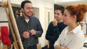 Glimlachende studenten en vrouwelijke kunstleraar die kunstwerk op schildersezel analyseren stock footage