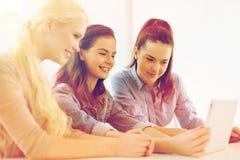 Glimlachende studenten met de computer van tabletpc op school royalty-vrije stock afbeelding