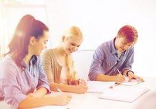 Glimlachende studenten met notitieboekjes op school stock foto