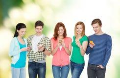 Glimlachende studenten met smartphones Stock Foto